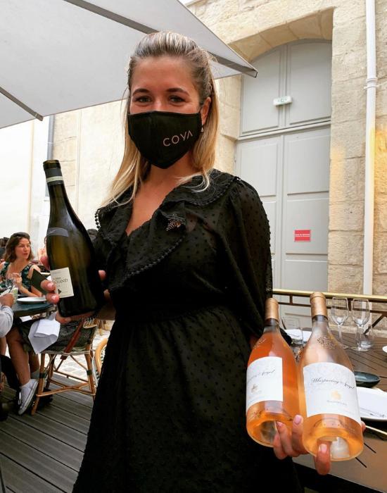 Anastasia  showcasing wine bottles at COYA post covid-19.